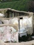 16. Un vecchio camino si ritrova circondato dall'erba, nella stanza affianco le finestre socchiuse